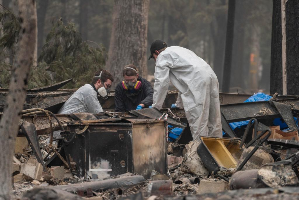 Three searchers crouch through the warped frame of a mobile home.