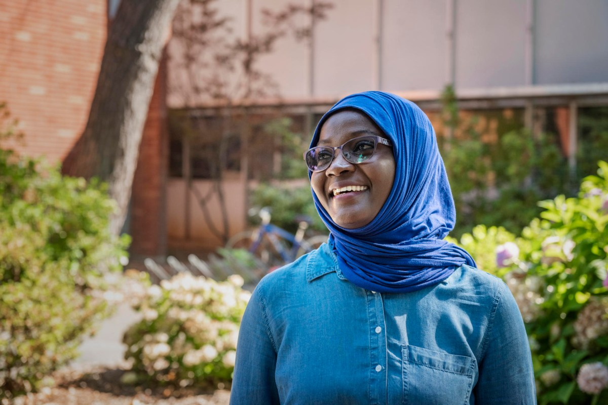 A teacher from Ghana smiles in front of classrooms, wearing a denim top and bright blue scarf on her head.