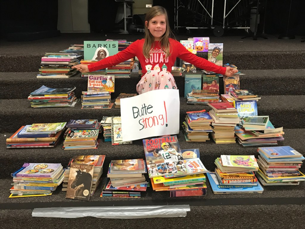 "Isla Aguilar sits among piles of books with a sign that reads ""Butte Strong!"""