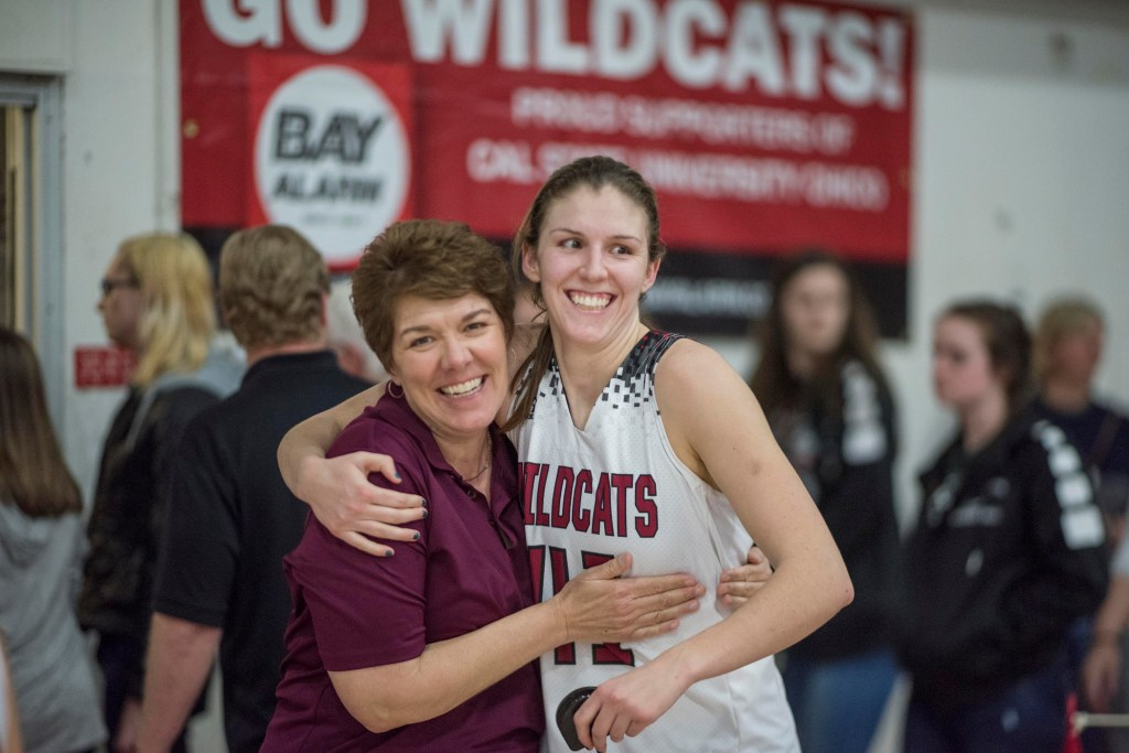 Anita wraps her arms around her daughter, who is wearing a Wildcats basketball jersey after a game.