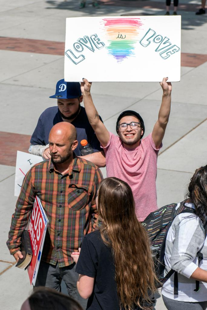 "Seve Christian (right) holds up a sign that reads ""Love is Love"" as students speak back against persecution on campus from one man who only wanted to be identified as Ron (left), expressing the difference of opinions about religious views about Jesus Awareness Day on Wednesday, April 13, 2016 in Chico, Calif. (Jason Halley/University Photographer)"