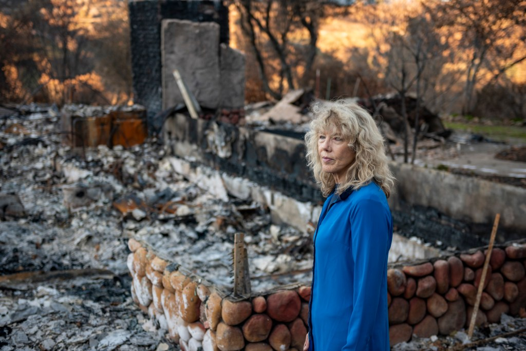 Cindy Wolff stands in front of the ashen rubble of her home, with a rock foundation all that is left.