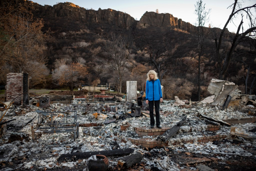 Cindy Wolff stares down at the ashes of her former home while standing on what used to be her back patio. The bricks are buried under layers of ashes and charred wood.