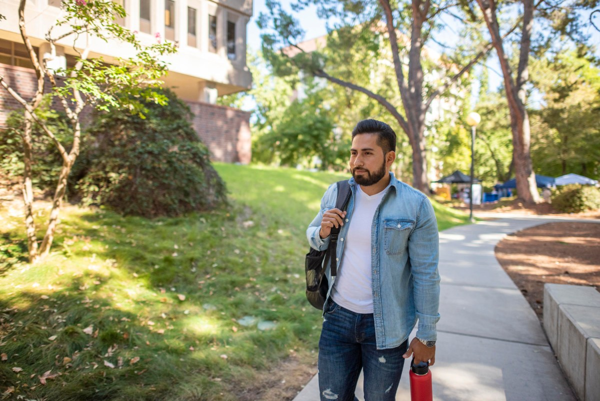 Jaime Valdovinos walks down a path near Plumas Hall with a backpack slung over his shoulder and reusable water bottle in hand.