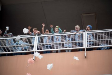 Children throw parachute toys off a ledge for Imagineer Day.