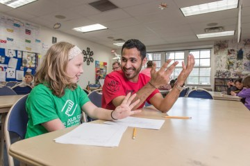"""Leah Reed, 10 (left), learns how to write in Arabic from CAVE Volunteer Yahya """"John"""" Al Maqboul (right) at the Boys & Girls Club on Monday, March 21, 2016 in Chico, Calif."""
