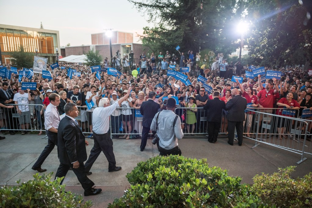 Bernie Sanders waves to a crowd of supporters waving signs as he exits.