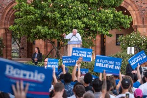 Bernie Sanders at a podium in front of a crowd waving signs.