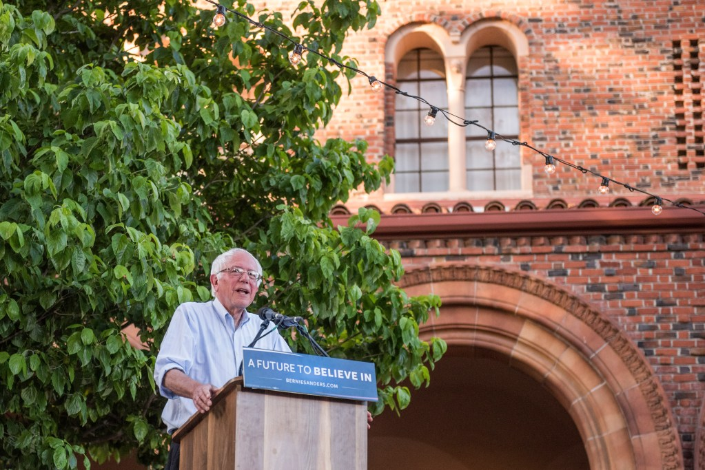 Bernie Sanders speaks at a podium in front of Laxson Auditorium.