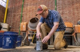 Tim O'Shea sprays water on a cylinder of concrete over a metal grate in the concrete lab.