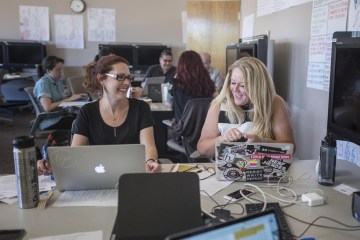 Faculty Janell Bauer and Kim Jaxon laugh as they work at their laptops during the grant boot camp.