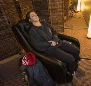 Annie Weiss relaxes in a massage chair in the Zen Den II.