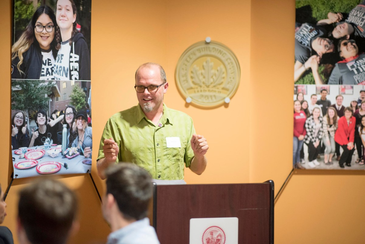 Chico State professor Garrett Liles stands a podium as he speaks to a crowd of students.