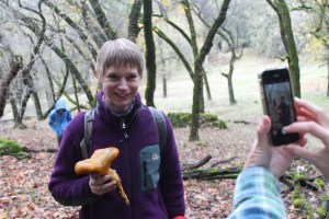 Dori Wall, a faculty member in the School of Education, poses with a jack-o'-lantern mushroom so someone can take her picture.