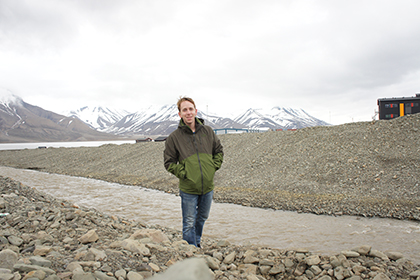 Matthew Stone standing beside a rocky stream with snow-capped mountains in the background,