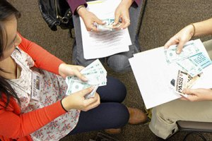 Three students count play dollars during a poverty simulation excercise in a Chico State classroom in 2013.