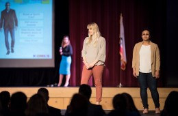 Showing outfits appropriate for casual work events, one woman student models a white blouse, tan jeans, and dress pumps. Another student wears a tan blazer, white silk blouse, and dark-wash jeans, and dressy flat shoes.