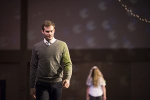 Male student dressed in a grey sweater, dress shirt, and tie walks on stage.