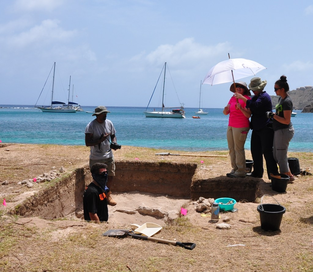 A group of researchers stand in an excavation site with the ocean in the background.