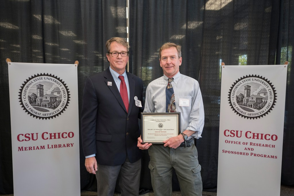 Gregory Watkins (right) is presented with the Professional Achievement Honor award by Kevin Kelley, interim associate vice president of the University's Office of Research and Sponsored Programs.