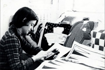 An old black and white photo of Jacki Headley using a calculator.