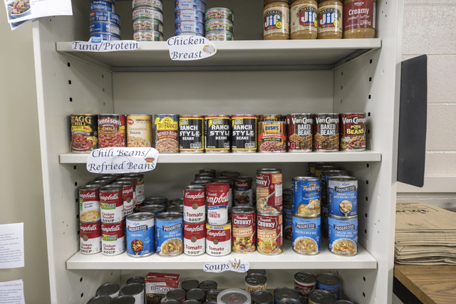 Several shelves of canned and jarred foods are displayed at the Hungry Wildcat Food Pantry.