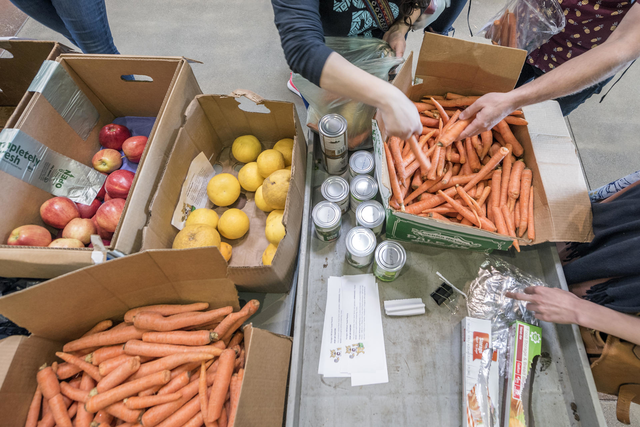 Several hands reach into boxes of carrots and apples to put them into bags during CalFresh Day.