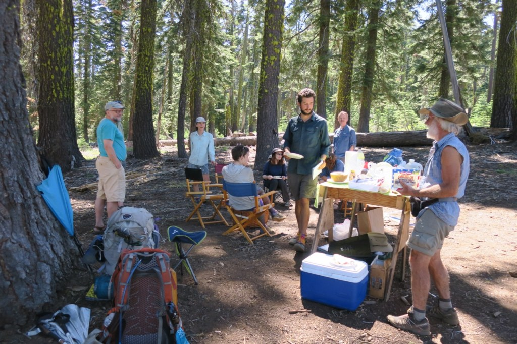 A group of hikers gather around refreshments and talk.