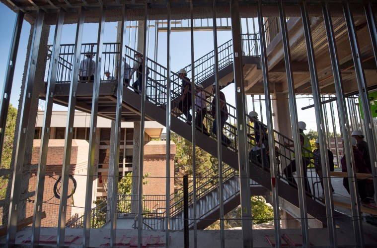 People climb the exterior staircase of the new building, as seen through the steel-framed walls.