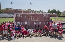 Alumni of the Chico State football team pose next to the old scoreboard.