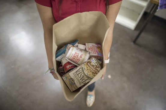 Shot looking down into a grocery bag held by a student, filled with pantry items such as pasta and noodles.