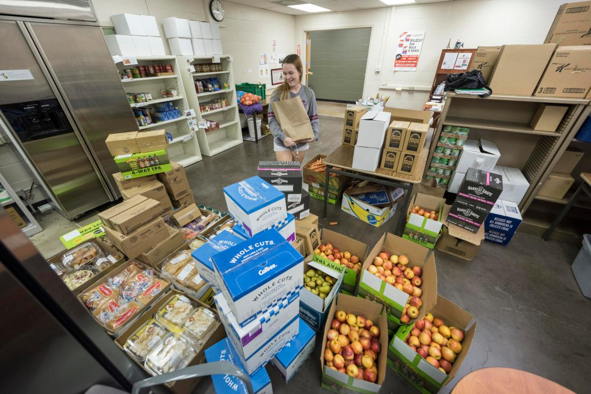 Hannah Horton carries a grocery bag as she looks through apples at the Hungry Wildcat Food Pantry