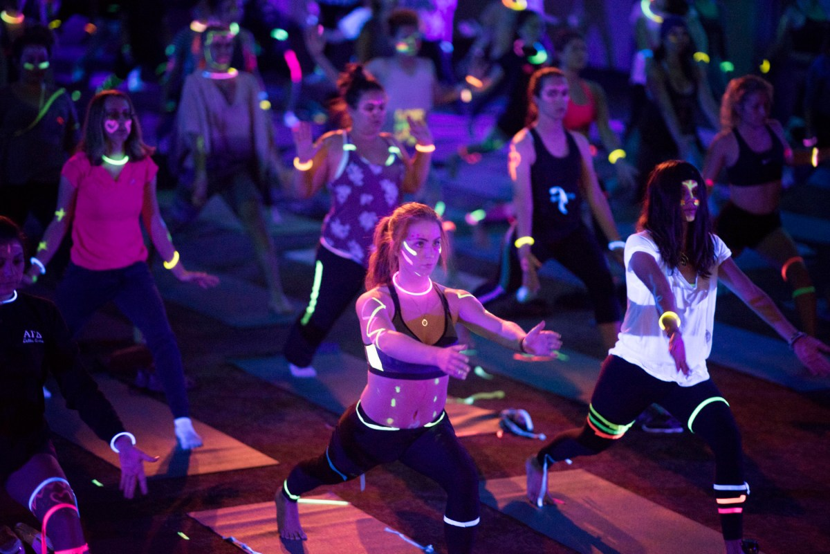 Students decorated with glow-in-the-dark body paint and glowstick necklaces and bracelets hold a yoga warrior pose in a darkened room.