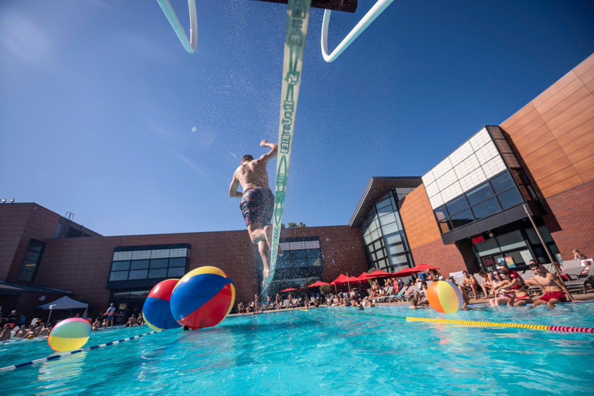 A student in swim trunks walks across a slackline hovering above the WREC pool as dozens of students sit on the side of the pool and watch, while giant inflatable balls float on the pool surface.