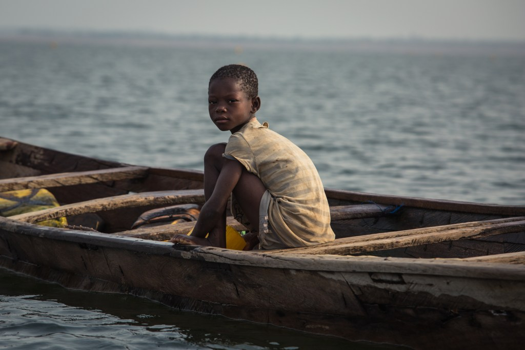 A child sits on a fishing vessel on Lake Volta. (Photo courtesy of Emily Teague)