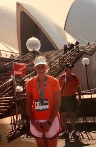 Vanden Bosch wearing running clothes, race bib, and a medal sits in front of the Sydney Opera House