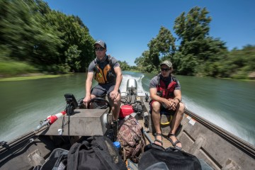 Graduate student Dylan Stompe (left) drives a boat along with Carlos Estrada (right) as students count salmon as part of a Summer Undergraduate Research Program (UGR) involved in the Chico STEM Connections Collaborative (CSC2) program on the Sacramento River on Wednesday, July 5, 2017 in Chico, Calif. (Jason Halley/University Photographer)