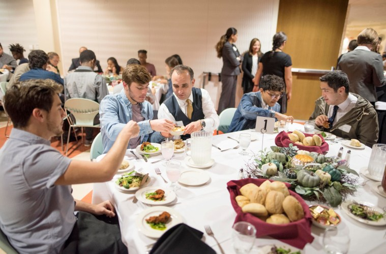 Students and faculty sit around a dining table enjoying a meal.