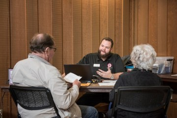A student assists two older adults with their taxes