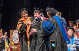 MBA graduate receives his master's hood from two faculty