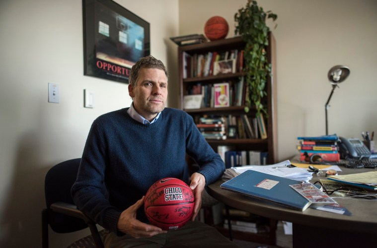 Carson Medley holding a basketball in his office