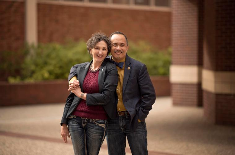 Renee Renner (left) and Ben Juliano (right) hold hands and pose for a photo on the Chico State campus.