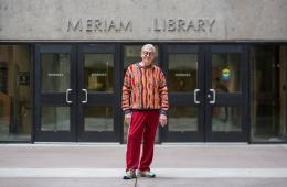 """Joe Crotts posing for a photo in front of the """"Meriam Library"""" sign in front of the library entrance."""