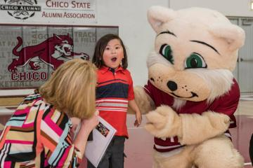 Willie the Wildcat mascot and a Make a Wish representative crouch next to a surprised child