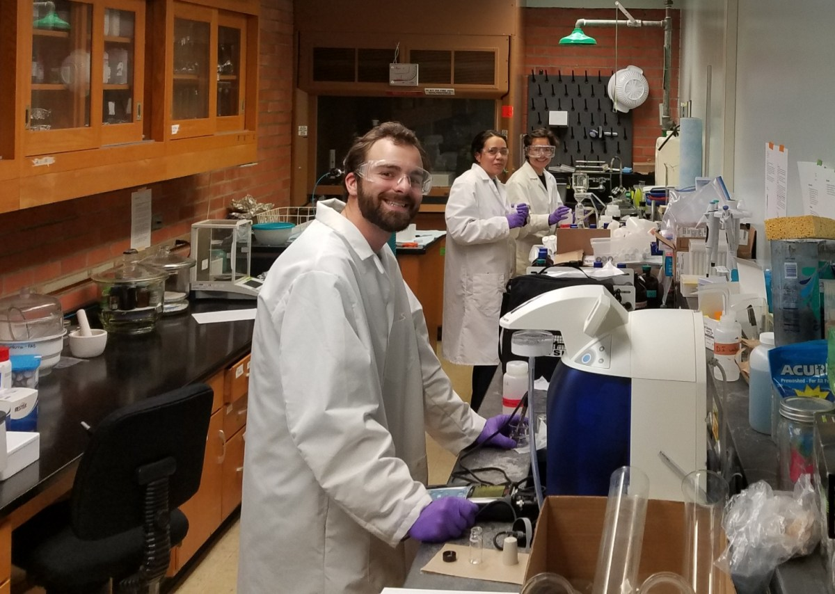 Students wearing white coats stand before an array of testing implements in a lab.