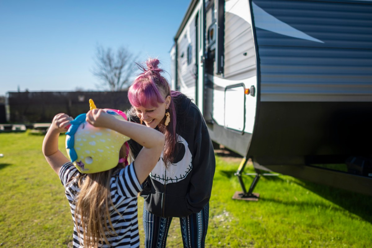 Sabrina Hanes stands outside her trailer and leans over to smile at her daughter as she adjusts her unicorn bike helmet.