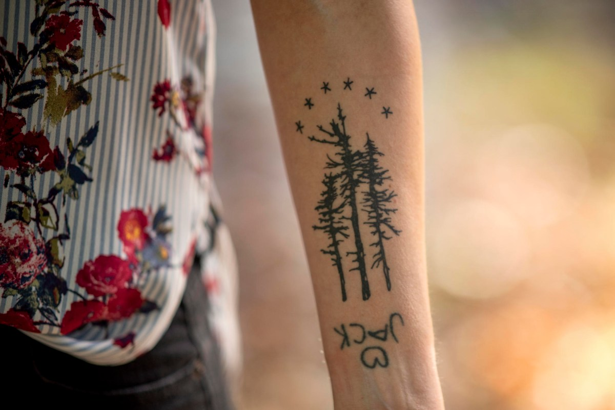 A tattoo on Tamara Bradford's forearm has thee pine trees, the word Jack with a heart above it, and six stars.