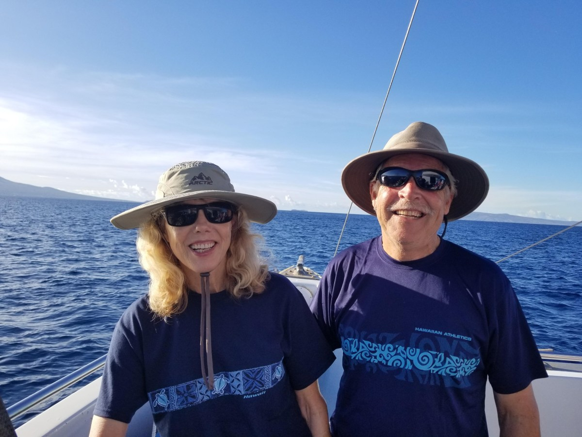 Cindy Wolff and her husband smile on a boat off the coast of Maui, with the ocean stretching behind them.