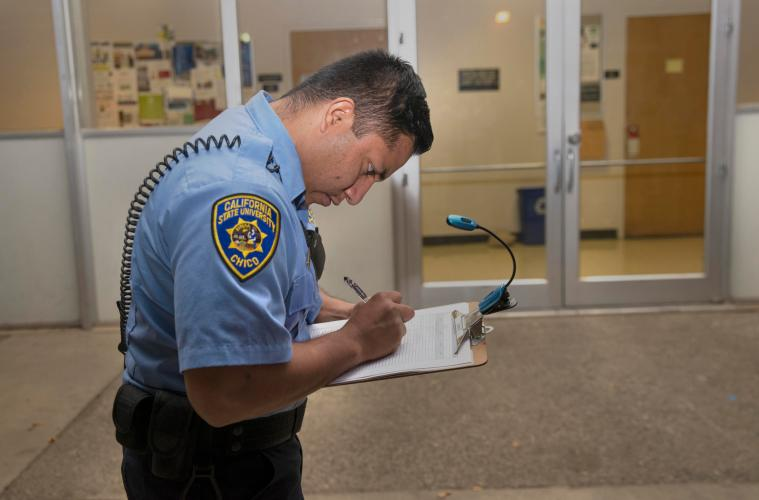 A member of the University Police Department makes marks on a list during a safety walk in 2015. A spring safety walk will take place around the University neighborhoods on Tuesday, March 13.