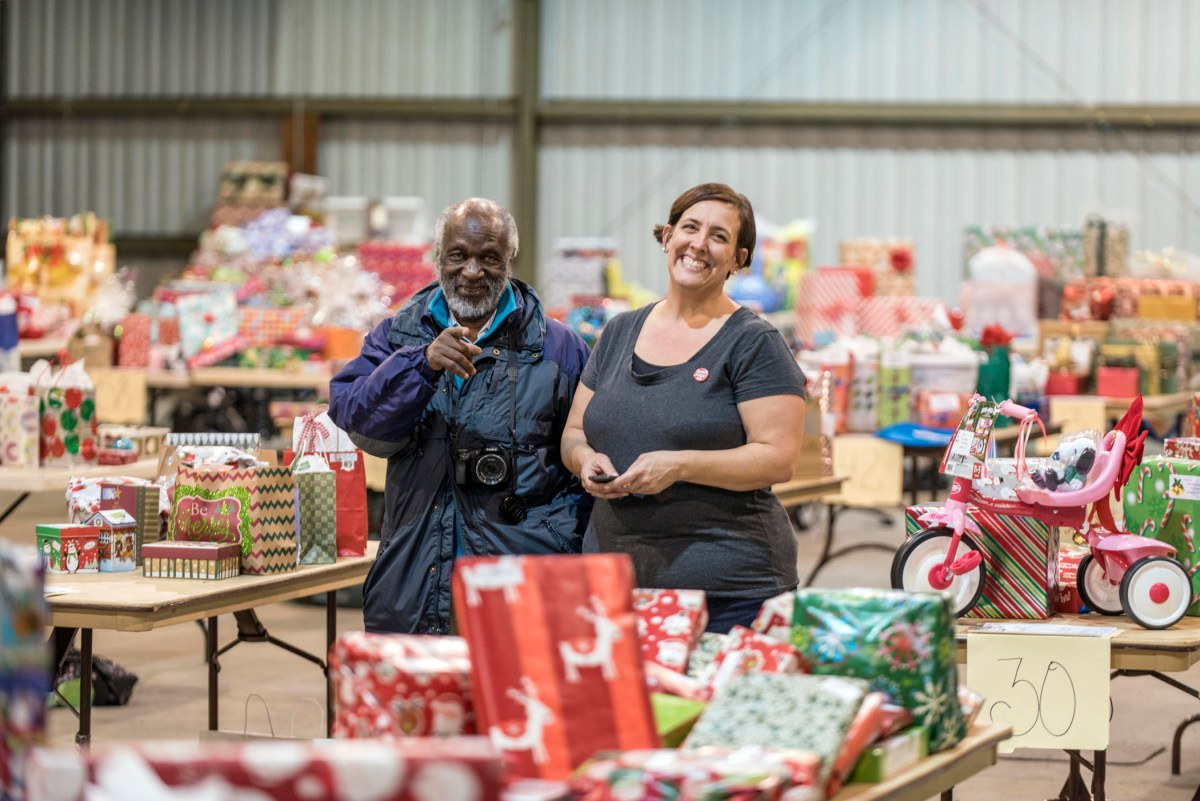 Two staff members smile while standing amid tables filled with wrapped gifts.